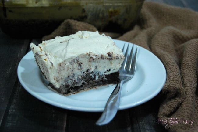 Brownie Ice Cream Poke Cake with Whipped Cream Peanut Butter Frosting - a chocolate dessert you're dying to try! #peanutbutterbash | The TipToe Fairy