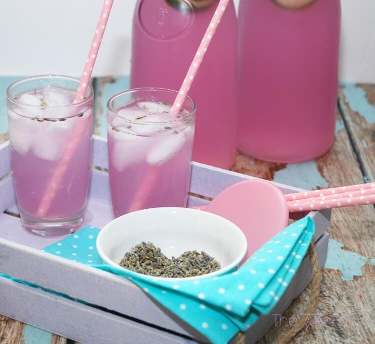 A different angle of the two glasses of Vanilla Lavender Limeade with the bowl of dried lavender centered.