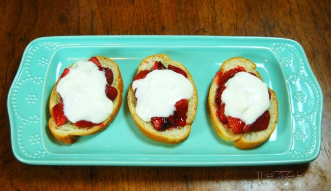 Three slices of roasted strawberry crostini on a blue platter