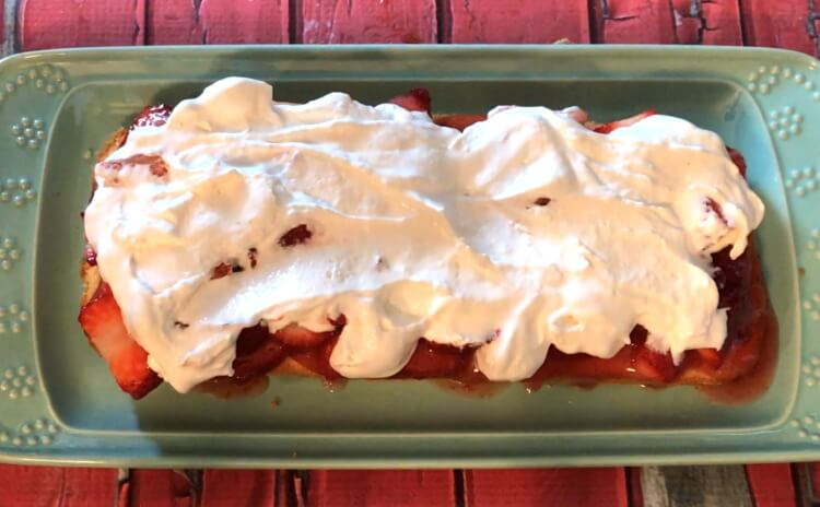 The bottom layer of pound cake slathered in strawberries and whipped cream.