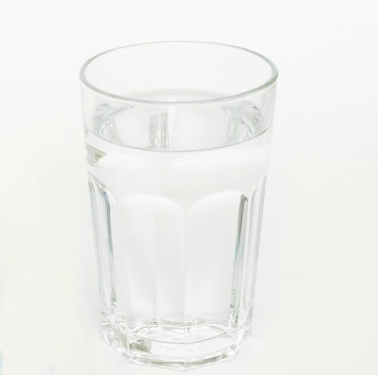 A clear pint glass full of water on a white background.