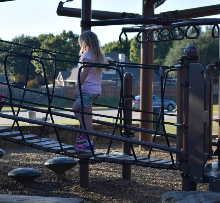 Navigating the bridge at an inclusive playground