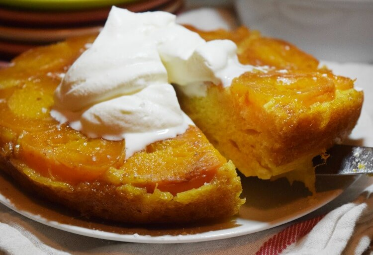 Lifting a slice up from the Apricot Upside Down Cake topped whipped cream.