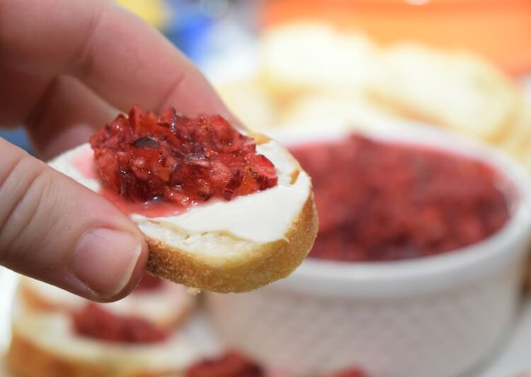 Cranberry Orange Relish on a slice of baguette topped with cream cheese.