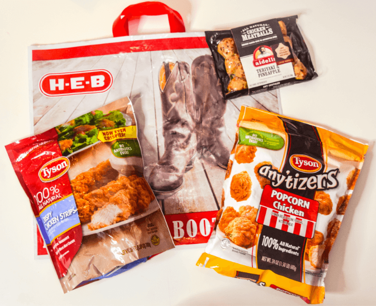 H-E-B reusable bag with packages of Tyson Crispy Chicken Strips, Aidells Meatballs, and Tyson Any'tizers Popcorn Chicken