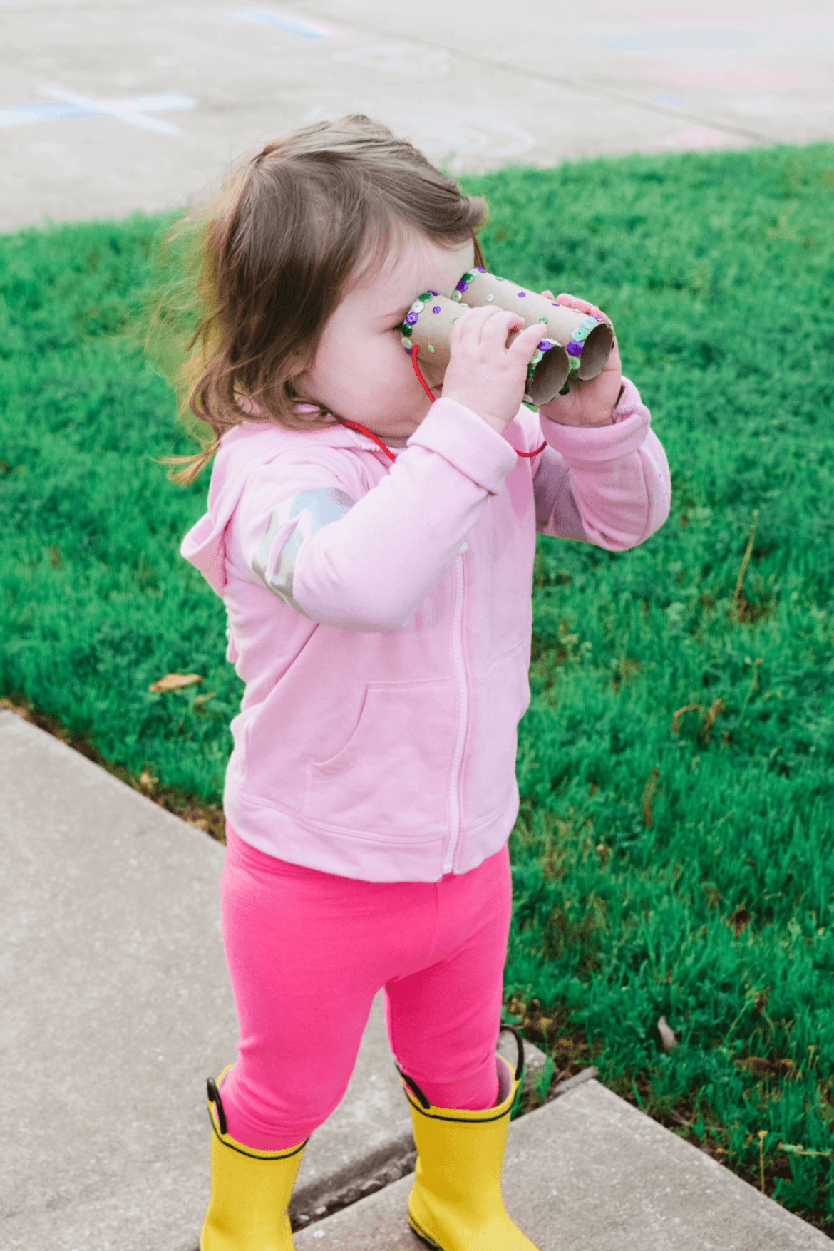 A toddler girl using her toilet paper binoculars for a neighborhood bear scavenger hunt