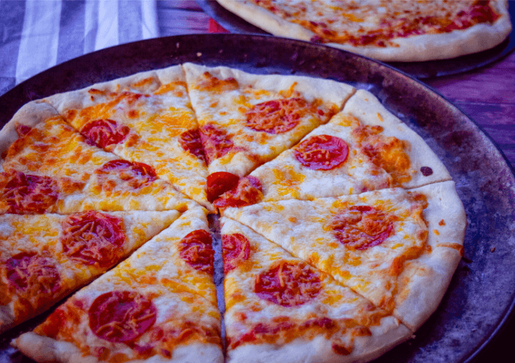 Pepperoni Pizza sliced up into 8 slices on a pan.