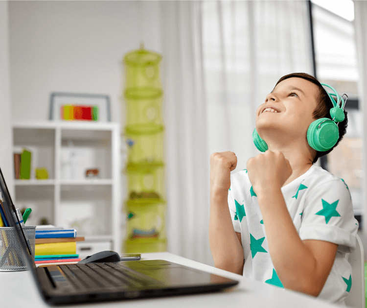 A boy with headphones on in front of his laptop making a winning pose with his fists.