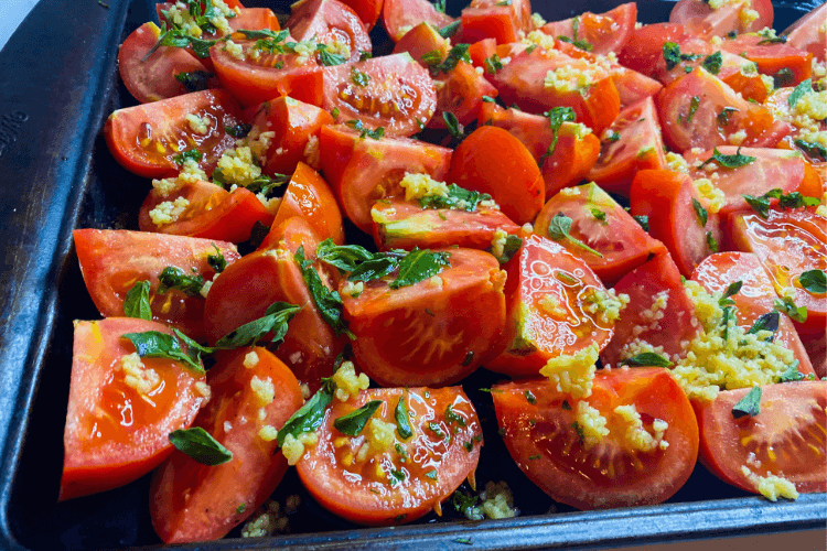 A baking sheet full of raw tomatoe quarters covered in herbs and minced garlic and olive oil.