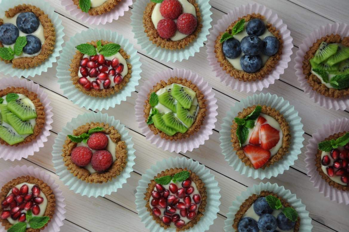 Rows and rows of single serving fruit tarts with a custard base and different fruit toppings like strawberries, raspberries, pomegrante seeds, and kiwi