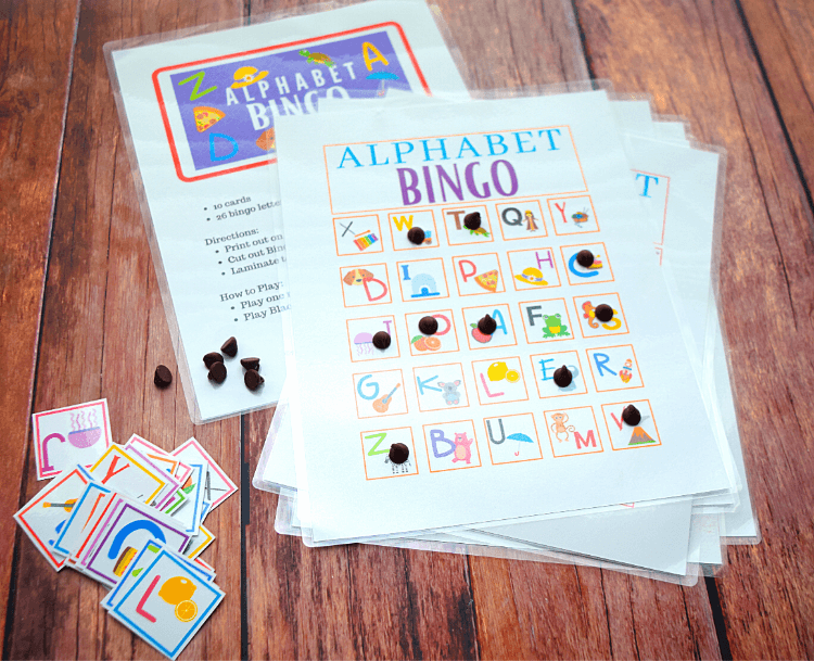 Alphabet Bingo with a pile of bingo cards and a pile of bingo chips with letters on them.