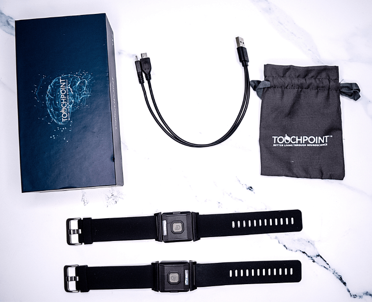 The TouchPoint wearables with the cable, box, and drawstring bag.