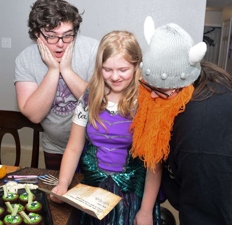 Teens and tweens reading over the starting letter for the Halloween escape room at home.