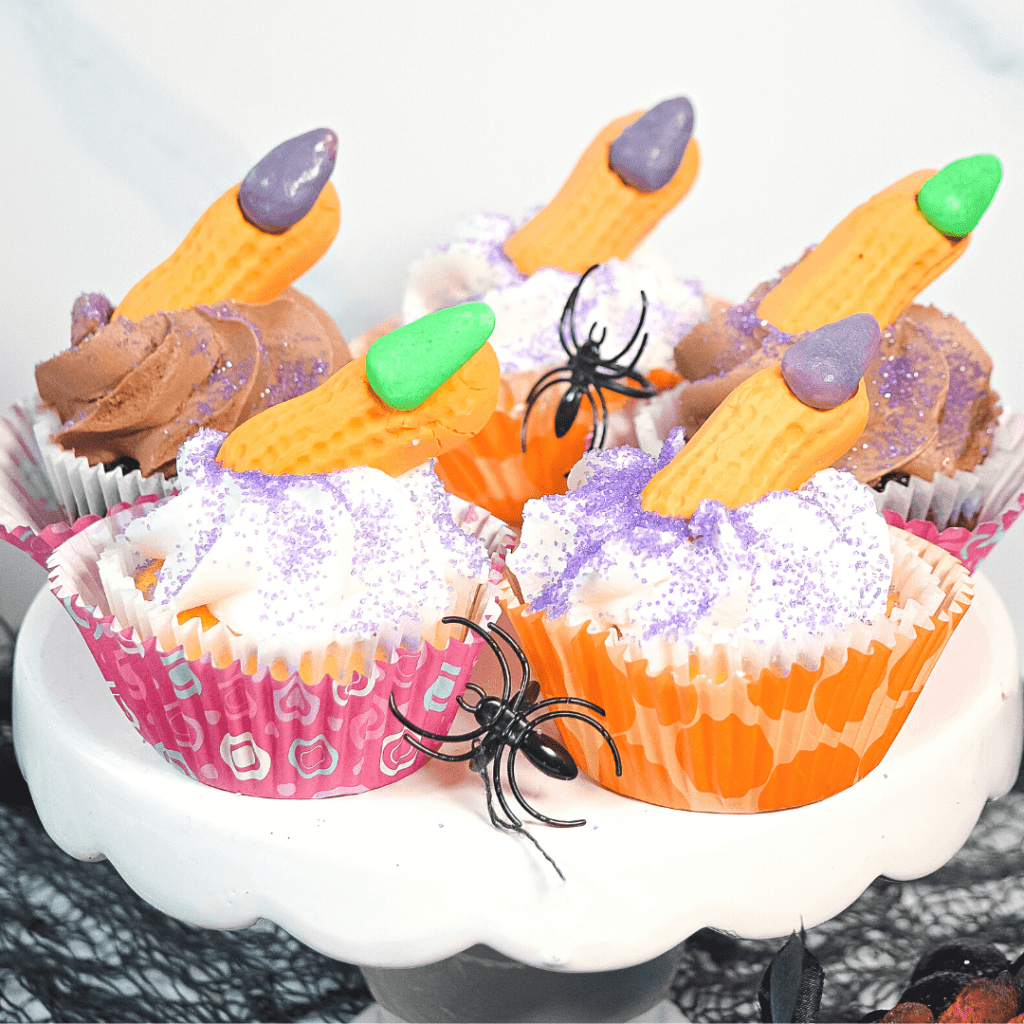 Close up image of five witch finger cupcakes with spider rings on a white pedestal