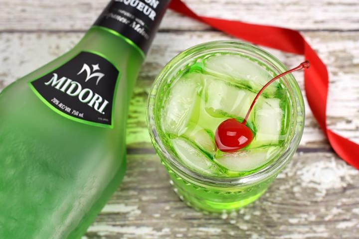 A bottle of midori beside a green cocktail.