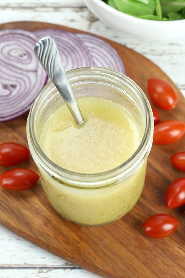 Overhead shot of salad dressing with a spoon in jar, on a cutting board with salad ingredients.