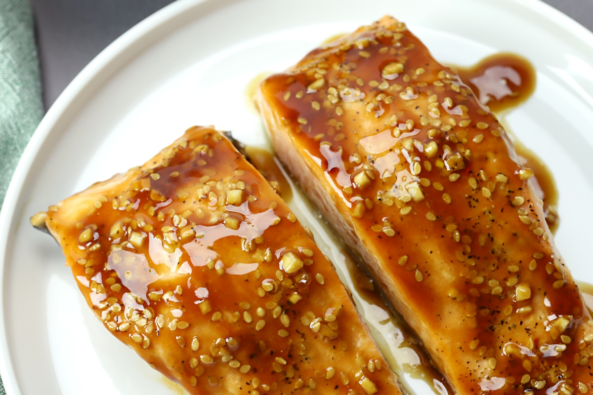 Two pieces of salmon topped with sesame seeds and ginger