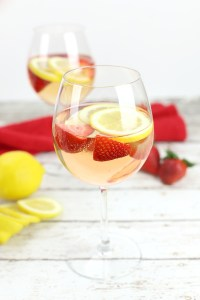 A wine glass filled with Rosé Sangria, with strawberries and lemon slices