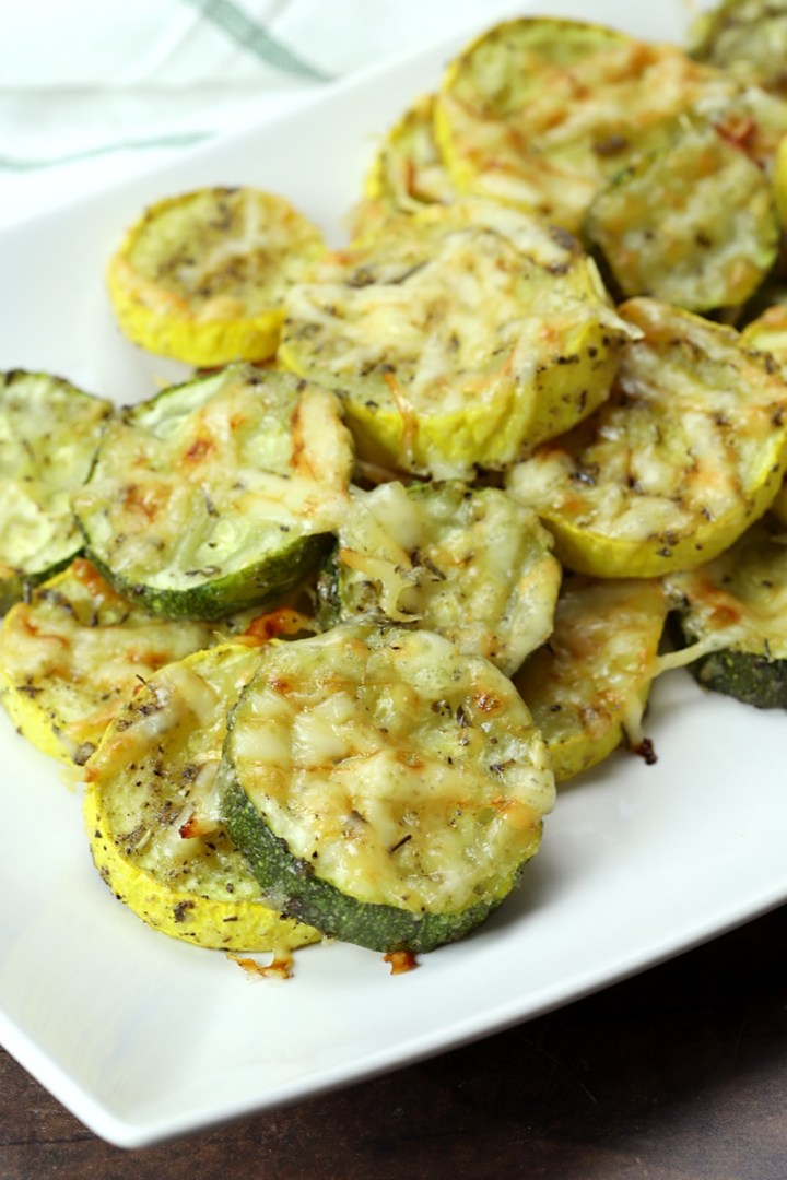 Zucchini and squash with melted parmesan cheese on a white serving plate.