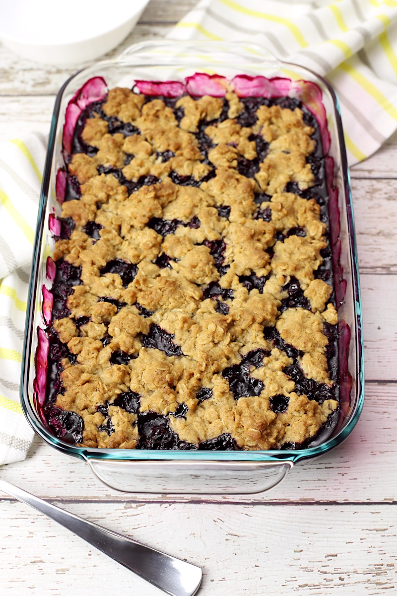 A baked pan of blueberry crisp on a white wood counter top.