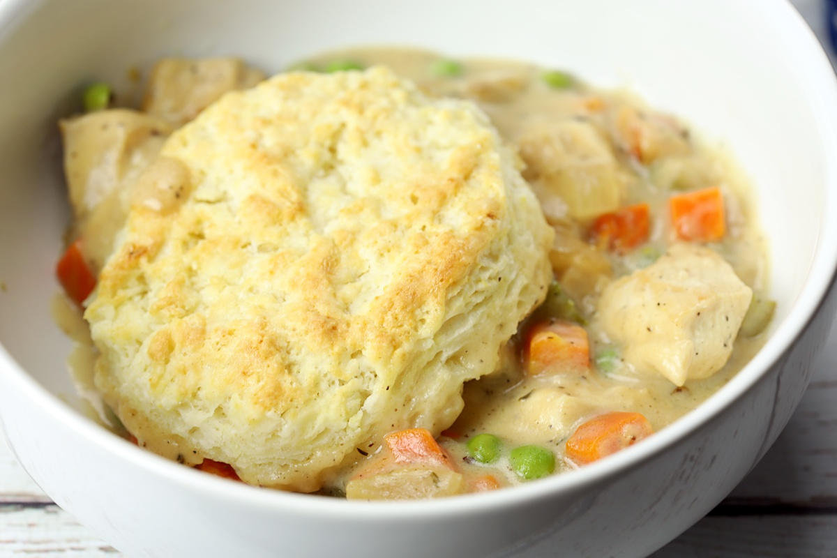 Biscuit topping chicken pot pie in a white bowl.