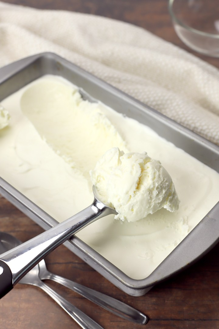 Vanilla ice cream being scooped by an ice cream scoop.