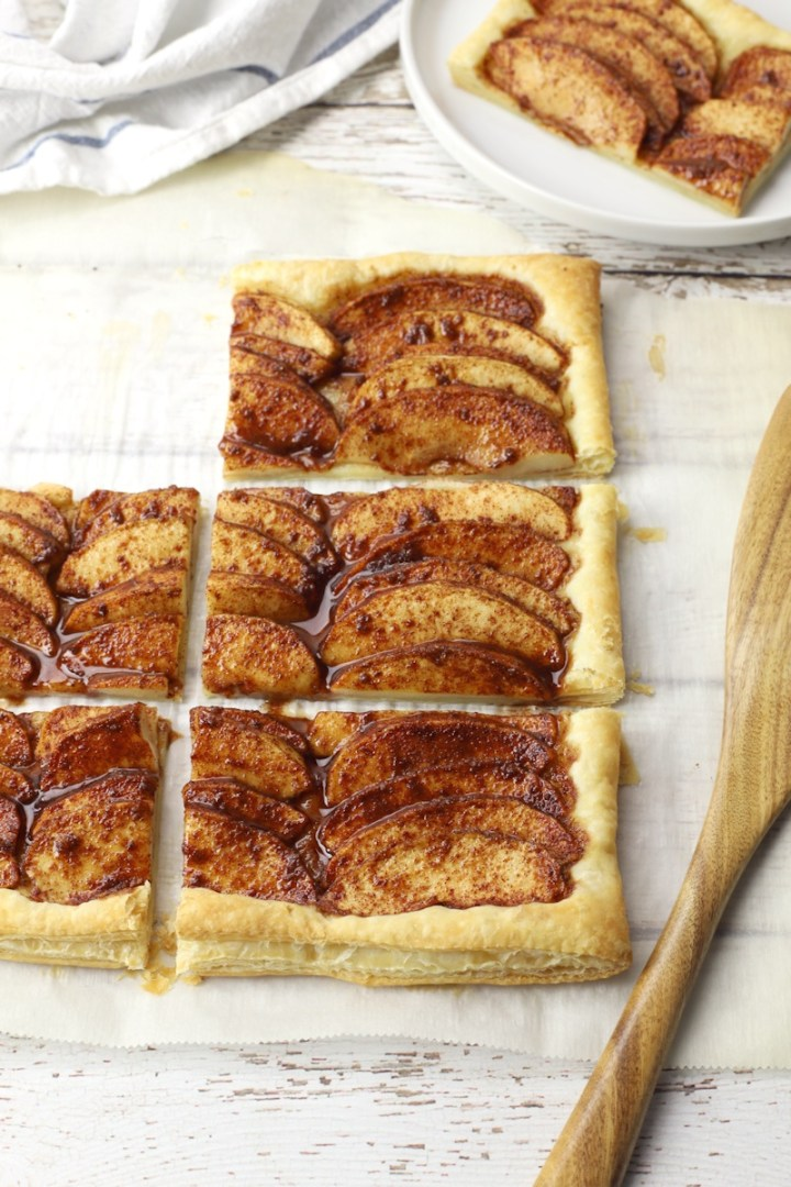 Apple tart ready to serve, six pieces with one on a white plate.