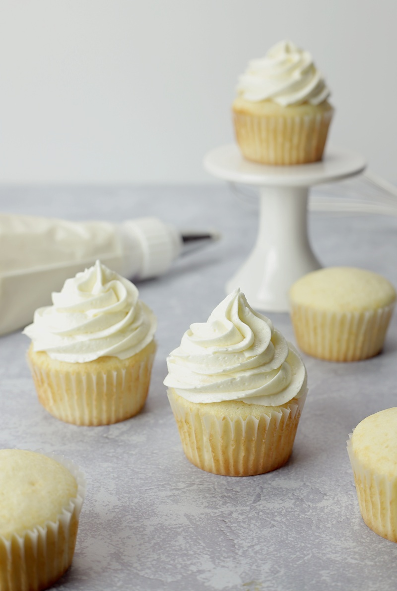 Several cupcakes, some frosted and some without, and a frosting piping bag.
