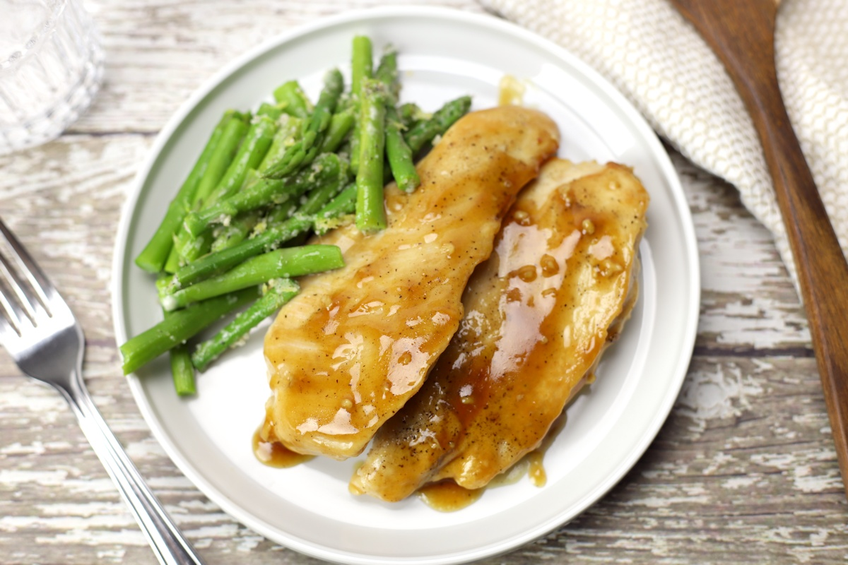 Maple glazed chicken with asparagus on a white plate.
