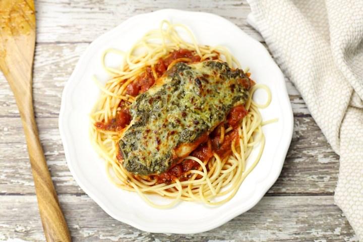 Pesto Mozzarella Chicken topping spaghetti on a white plate.
