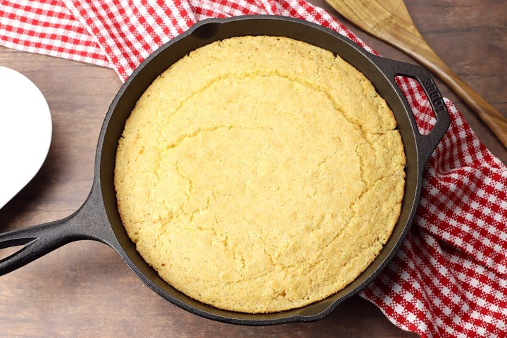 Skillet cornbread on a wood counter top with red checked towel.