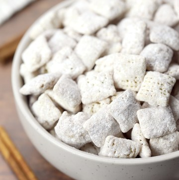 Puppy chow in a bowl on a wooden counter top.