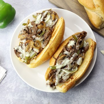 Two cheesesteak sandwiches on a white plate.
