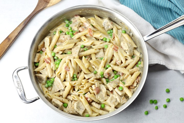 A saute pan filled with leftover turkey alfredo skillet meal.