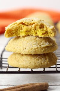 Stack of pumpkin sugar cookies on the edge of a cooling rack.