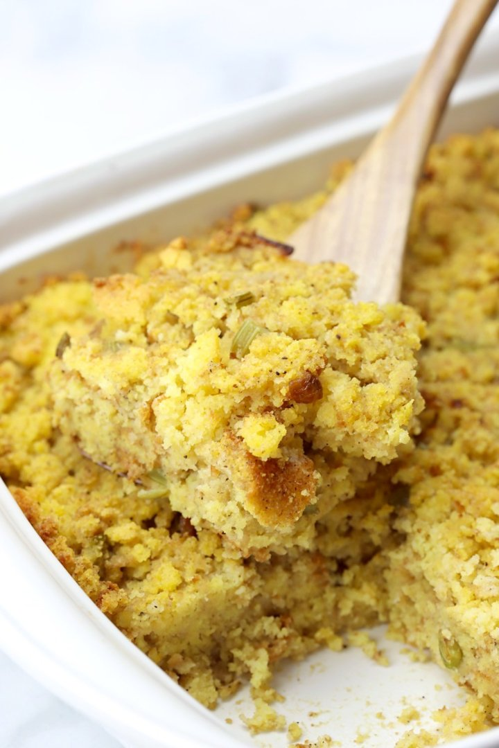 A wooden spatula lifting a serving of cornbread dressing from a pan.