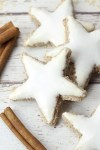 Zimtsterne cinnamon star cookies on a white counter top with cinnamon sticks.