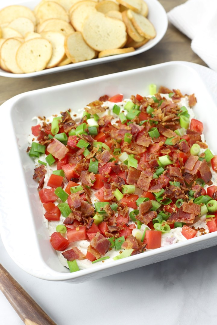 A plate of BLT Dip with bagel chips, ready to serve.
