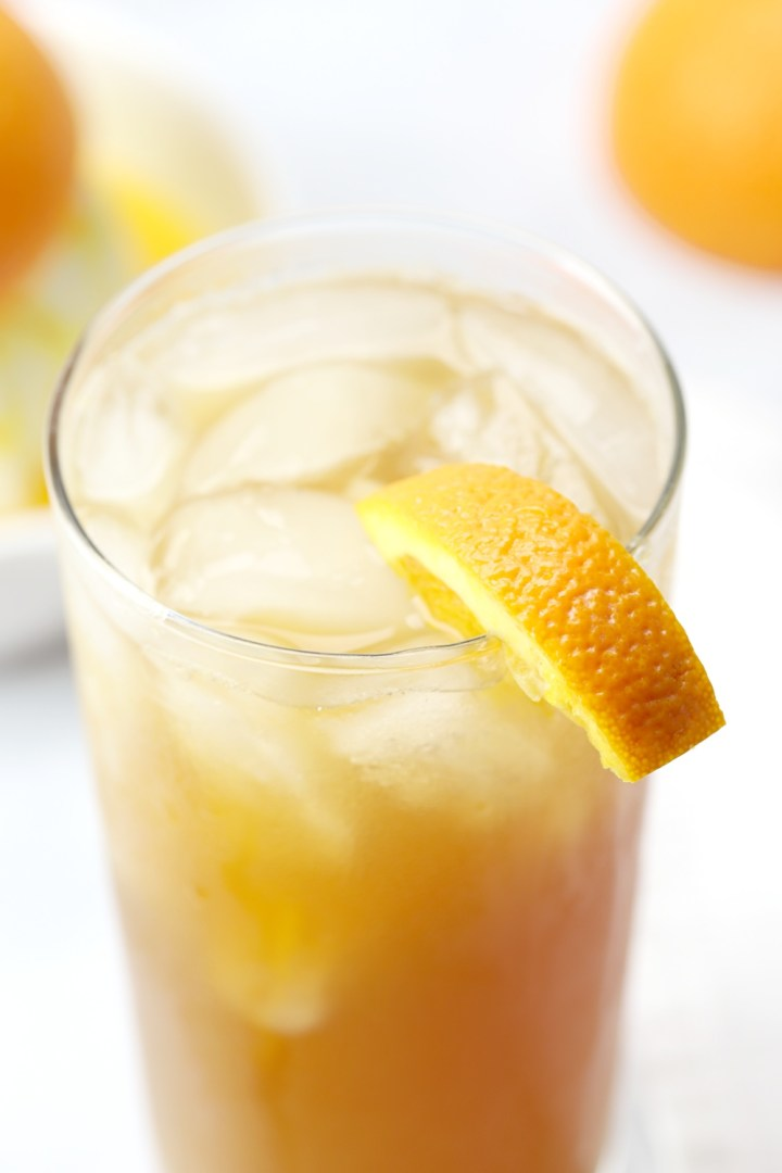 A glass of fireball orange sweet tea with an orange slice on the rim.