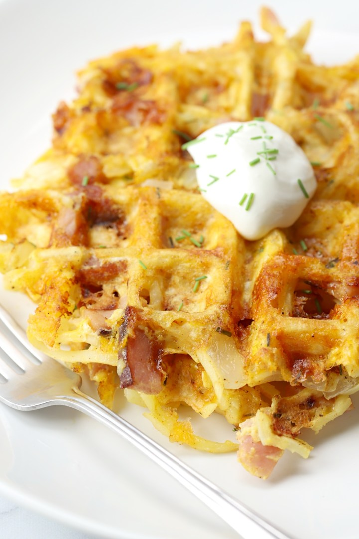 Dollop of sour cream and chives on top of savory waffles.