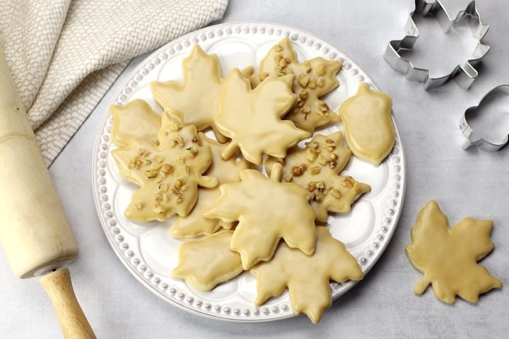 A decorative plate filled with maple leaf cut out cookies.