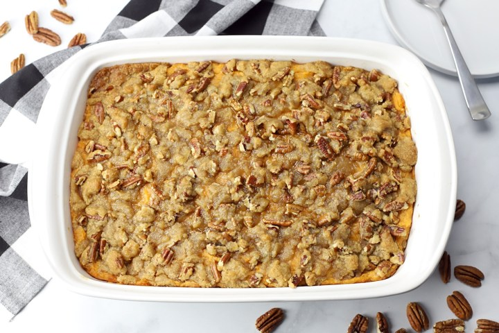 Sweet potato casserole in a white pan with a black and white checkered towel.