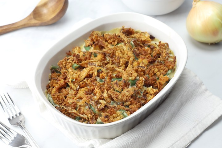 A white casserole dish filled with green beans and fried onions.