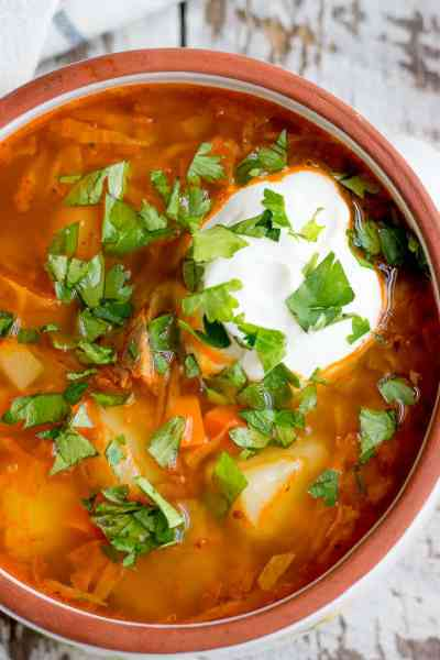 Russian cabbage soup with beef, topped with sour cream and parsley.