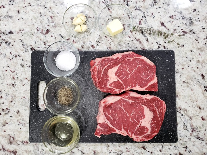 Ribeye steaks on a cutting board with salt, pepper, and oil.