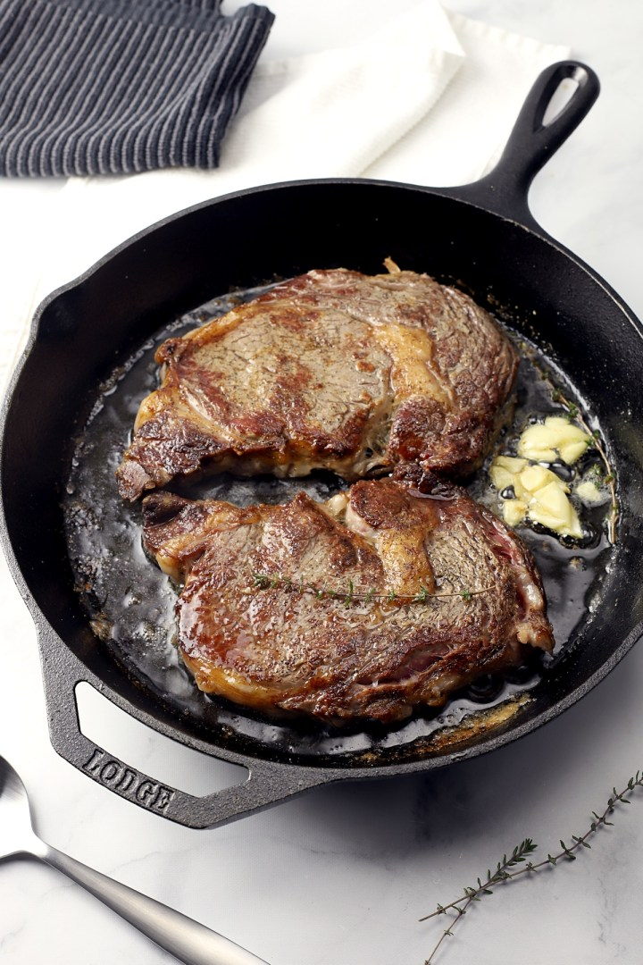 Cast iron pan with two steaks.