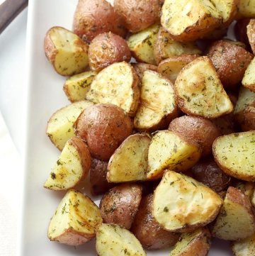 Quartered red potatoes coated in ranch seasoning on a serving plate.