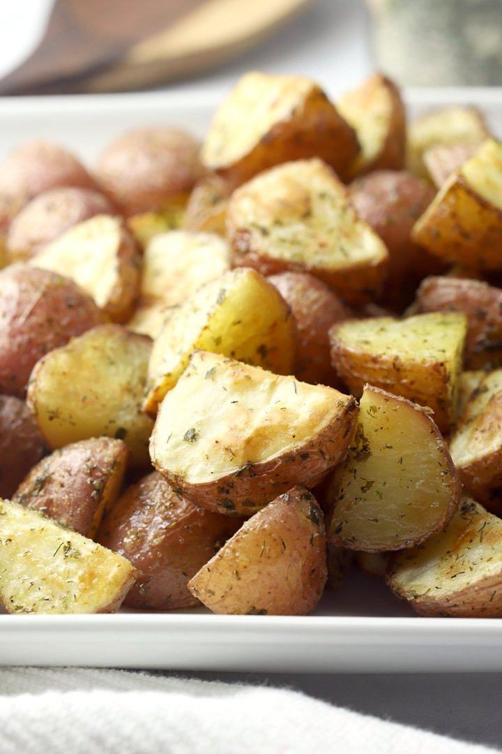 A white plate filled with red potatoes.
