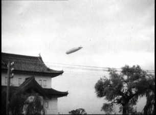 Graf Zeppelin in Japan, behind a traditional Japanese building.