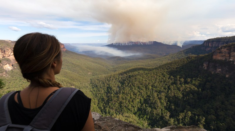 Woman watches as Australian bushfire rages on